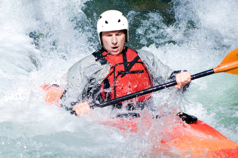 picture of man whitewater kayaking wearing a helmet